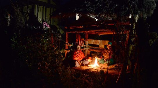Nepalese women sit by a fire in a chhaupadi hut.